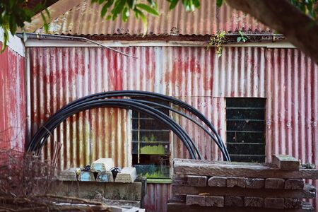 Abandoned old country shack with faded paintwork on corrugated iron walls and roof, with assorted hunk piled in front of it Stock Photo