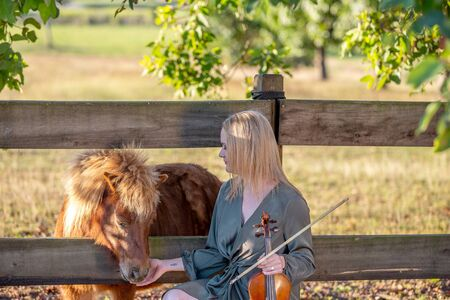 Woman holding out her hand for miniature pony to nuzzle as she holds a rare antique French violin