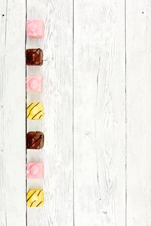 Row of miniature colorful iced cakes on board background with space for copy text, top view flat lay Фото со стока