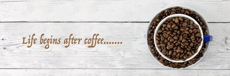 Coffee in cup and saucer with beans on timber board background flatlay top view with coffee saying text