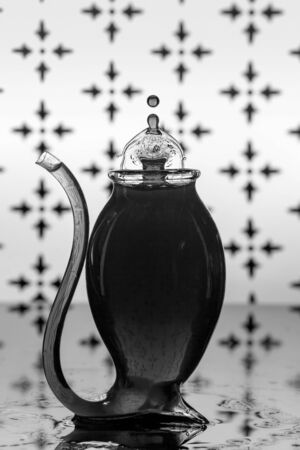 Water drops splash into a port glass against a patterned background to form an interesting shape, monotone flash photography