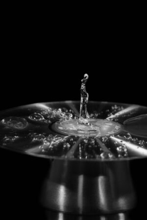 Drops of water splashed onto a cd form the figure of a lady dancing, monotone flash photography Imagens