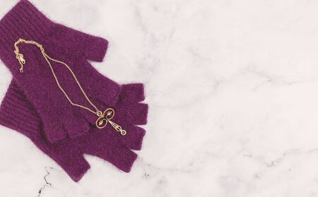 Delicate vintage rose gold fine filigree pendant with blue stones on red wool gloves with text copy space