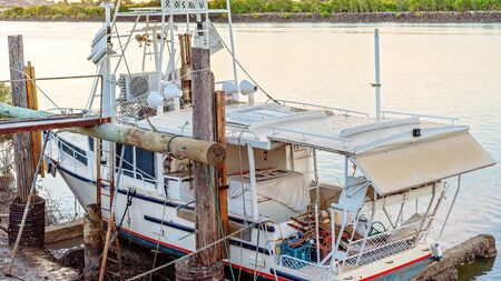 A commercial fishing boat moored at an old wooden dock on an Australian river while undergoing repairs