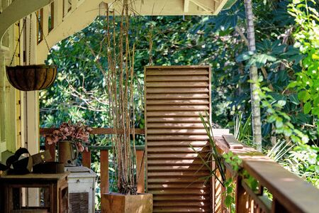 A collection of old dirty junk furniture on a wooden verandah of a home surrounded by bushland