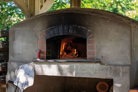 Large old stone and brick outdoor pizza oven with wood fire burning Stockfoto