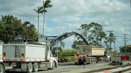 Mackay, Queensland, Australia - July 2019: Bitumen being sprayed into a trailer as part of roadwork infrastructure building a new highway overpass Stockfoto - 133173515