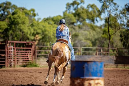 Female horseback rider competing in barrel racing at outback country rodeo