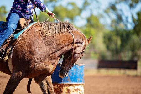 Close up of competitor on horseback making a figure eight turn in a barrel race at outback country rodeo Standard-Bild