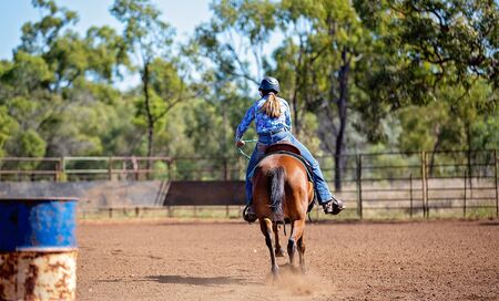 Young female horseback rider competing in barrel racing at outback country rodeo Stock Photo