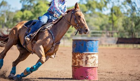 Close up of competitor on horseback making a figure eight turn in a barrel race at outback country rodeo Stok Fotoğraf
