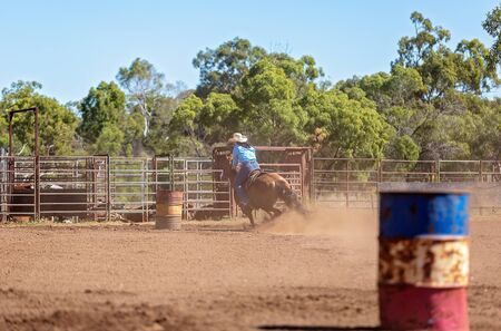 Competitor on horseback making a figure eight turn in a barrel race at an outback country rodeo
