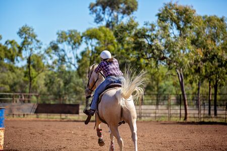 Female equestrian competing in barrel racing in dusty arena at outback country rodeo