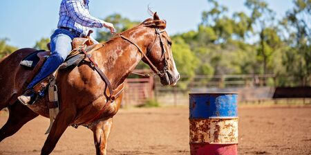 Close up of competitor on horseback making a figure eight turn in a barrel race at outback country rodeo