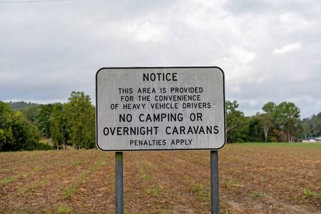 No camping or overnight caravans sign at a highway rest stop in a rural setting