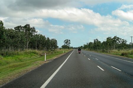 Motor cycle rider traveling fast on a country highway Фото со стока - 129924982