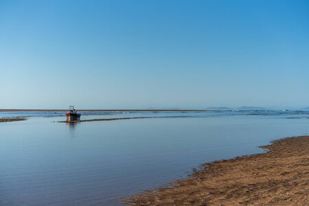 Small fishing boat moored offshore at low tide on a beautiful sandy Australian beach Stock Photo