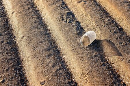 Broken plastic bottle discarded as rubbish on the sand - littering the environment 版權商用圖片 - 129925051