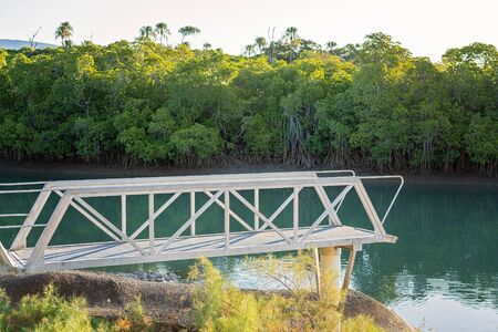 Small jetty jutting out from the bank of a mangrove creek near the beach, popular with fishermen