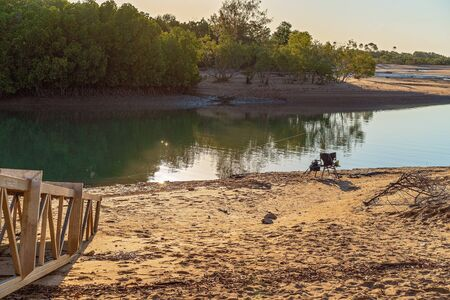 A fishermans empty chair on a sandy creek bank with line in the water ready to hook a fish Stock Photo