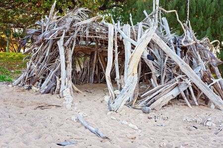 A crudely constructed fun shelter made from driftwood and palm leaves on an Australian beach
