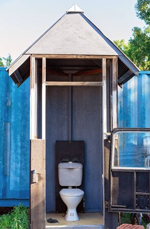 A crudely built and comical timber outdoor toilet enclosed by a car door and window Standard-Bild