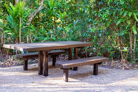 Outdoor picnic table and bench seats in a lush green bushland setting Stock Photo