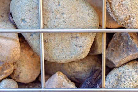 Rock retaining wall held together by steel rods in close-up Stok Fotoğraf