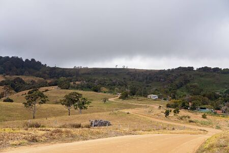 A dirt road winding its way through the rolling hills of drought-stricken Australian dairy farm on top of a mountain range