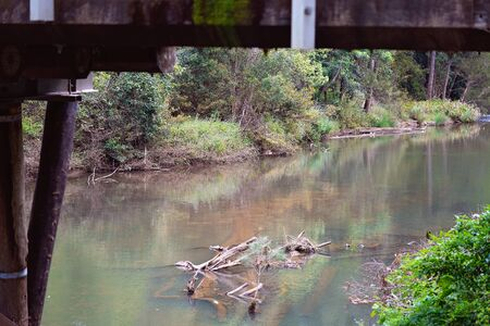 A calm and peaceful tropical rainforest creek framed by the bridge over it