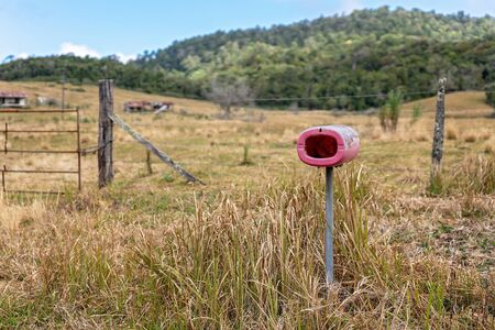 An old red plastic letterbox standing in front of an abandoned dairy farm property in rural Australia Banque d'images