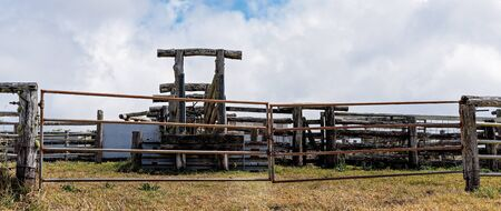 Old timber cattle yards used for herding cows to brand them now locked beyond a steel gate