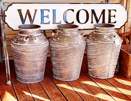 Three large decorative ceramic pots for sale in front of a metal welcome sign in a market shop