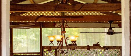 A rustic chandelier hanging from old wooden beams amongst farming objects in a country cafe