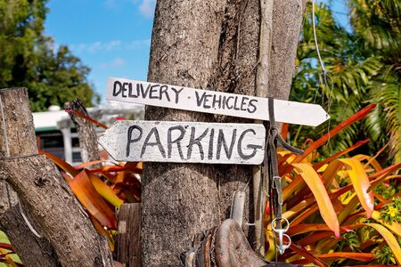 Hand written delivery vehicles and parking signs pointing to appropriate areas nailed onto a tree trunk above an old saddle and bridle at a casual country cafe Banco de Imagens
