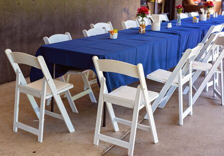 A long outdoor casual dining table with blue tablecloth and white chairs left in disarray after guests have left