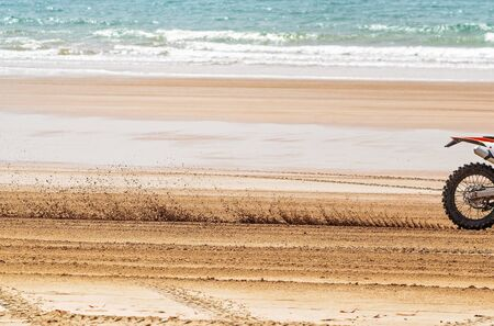 A close view of the blurred sand stirred up by a motorcyclist racing fast along the beach Фото со стока