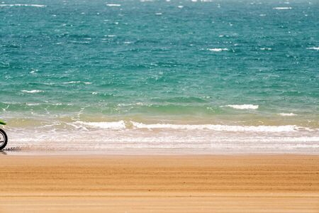 Ocean waves as a speeding motorbike races by on the sand Фото со стока
