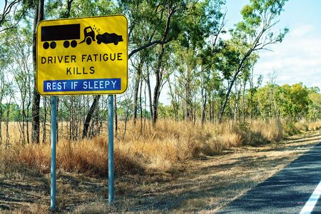 A yellow and black driver fatigue causes crashes alert sign on highway
