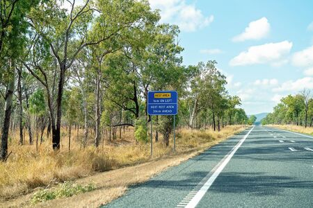 Rest area distance indicator sign on long straight Australian highway