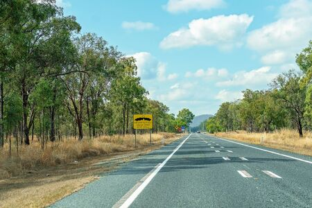 A yellow and black driver fatigue causes crashes alert sign on long straight Australian highway