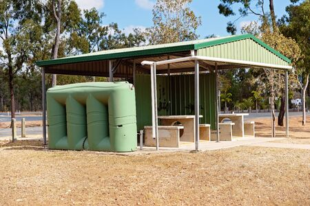 A shade rest stop area with seating and tank water for drivers to rest along their journey