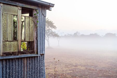 An old abandoned corrugated iron hut against a foggy landscape in early morning