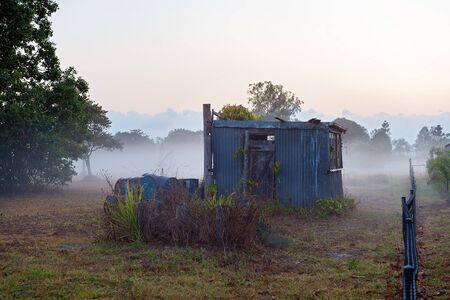 An old abandoned corrugated iron hut in a foggy country landscape in early morning