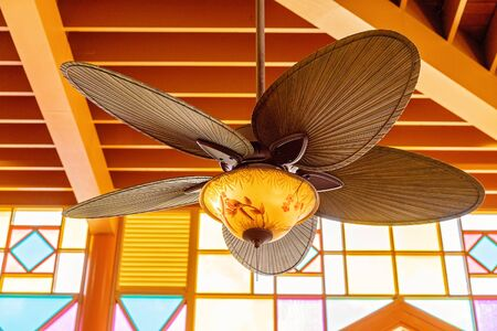 A decorative art deco style fan hanging from a timber ceiling against bright colorful lead-light windows