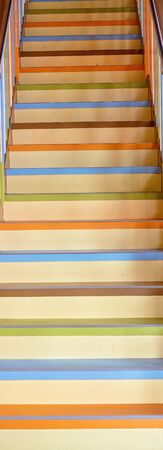 A colorful retro staircase with painted treads and railings