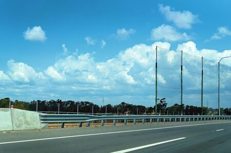 Highway guard rail and high wire netting to prevent flying debris on a busy main arterial highway
