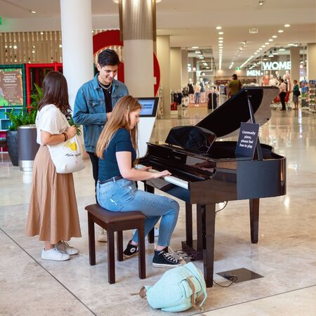 Brisbane, Queensland, Australia - 25th September 2019: A young woman playing a piano for community use in a busy shopping centre