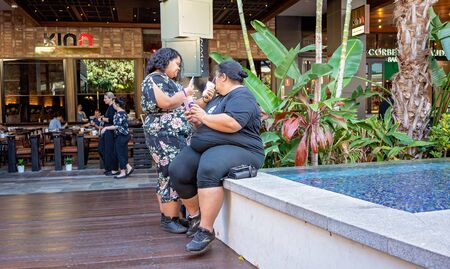 Brisbane, Queensland, Australia - 25th September 2019: Two overweight women drinking a milkshake each as they relax by the pool of a shopping centre Stockfoto - 133173853