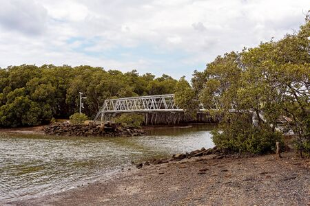 Steel bridge over a creek at low tide joining two mangrove banks